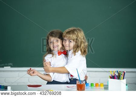 School Friends Hugging. Two School Kids, Girl And Boy Holding Hands Going At School Class In Classro