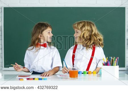 Children Doing School Lesson At Class. Funny School Girl An Boy Pupil Drawing A Picture. Cute Little