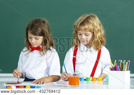 Children In Drawing School Lesson At Class. Funny School Girl An Boy Pupil Drawing A Picture. Cute L