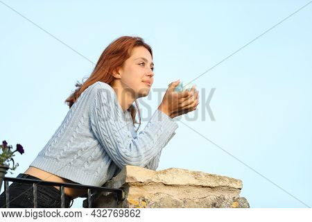 Happy House Owner Drinking Coffee From Cup Contemplating Views In A Balcony