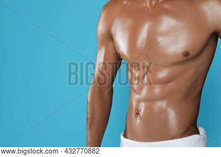Shirtless Man With Slim Body And Towel Wrapped Around His Hips On Light Blue Background, Closeup