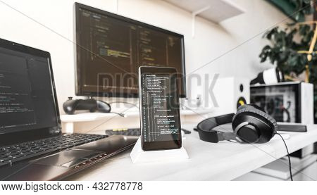 Close-up Smartphone Screen With Program Code. Workplace By Programmer With Pc And Laptop And Other D