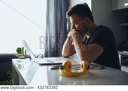 Concerned Serious Man Lost In Thoughts In Front Of Laptop, Focused Male Thinking Of Problem Solution