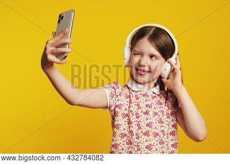 Little Girl Kid Shows Tongue And Blinks Eye While Takes Selfie On Smartphone Device, Listening Music