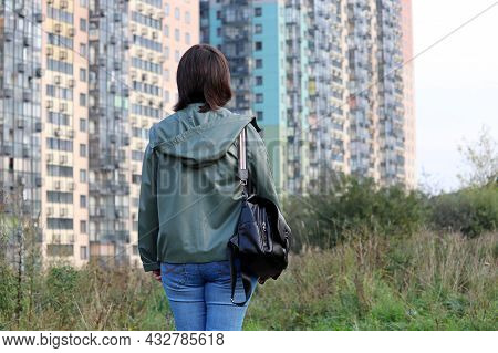 Woman Standing On Green Hill Overgrown With Grass And Looking To New Residential Buildings. Real Est