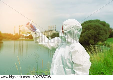 Sampling From Open Water. A Scientist Or Biologist Takes A Water Sample Near An Industrial Plant. A