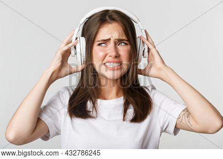 Close-up Of Annoyed Beautiful Girl In Wireless Headphones Complaining Awful Music, Grimacing Bothere