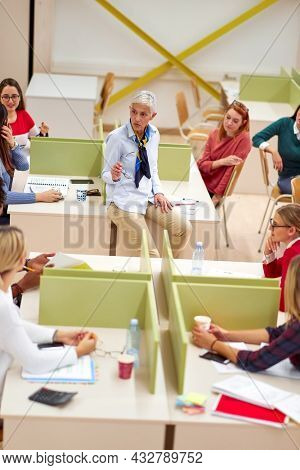 Female professor grabbing students attention by the lecture in the university classroom. Smart young people study at the college. Education, college, university, learning and people concept
