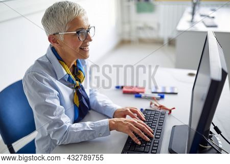 A female professor in front of a computer desk at the informatics lecture in the university computer classroom. Professor working at the college. Education, college, university, learning concept