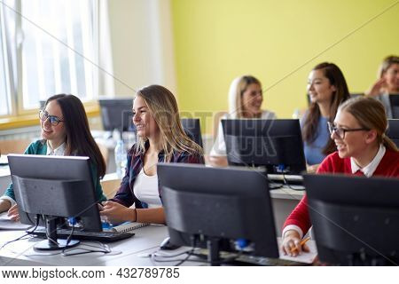 Students at an informatics lecture in the university computer classroom. Smart young people study at the college. Education, college, university, learning and people concept
