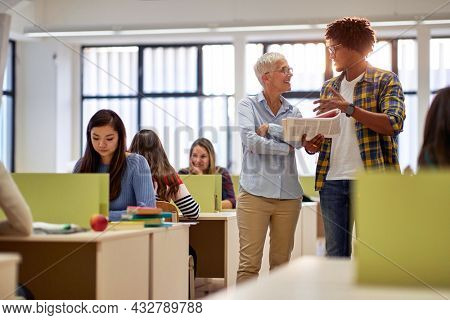 Male student discussing the lesson with female professor in the university classroom