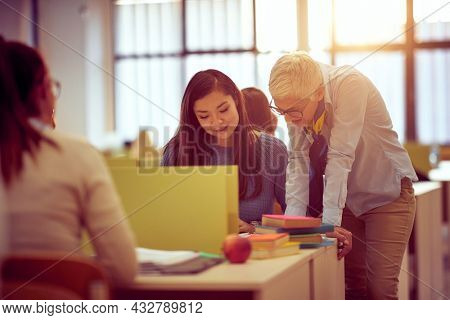 Female professor helping female student about the lesson in the classroom