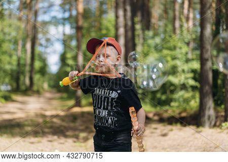 Cute Caucasian Boy Blowing Huge Soap Bubble . High Quality Photo
