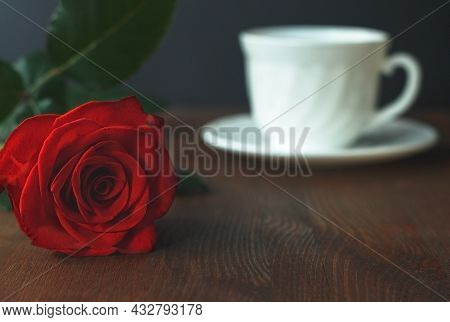 Beautiful Red Rose And White Cup Of Hot Tea Coffee On Wooden Background.