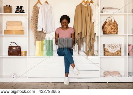 Black Female Shopaholic Using Laptop Shopping Online Purchasing Clothes Indoor
