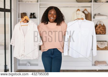 Black Lady Shopaholic Holding Shirts Choosing Buying Clothes In Store