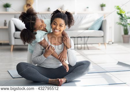 Beautiful Black Mother And Daughter Cuddling While Exercising