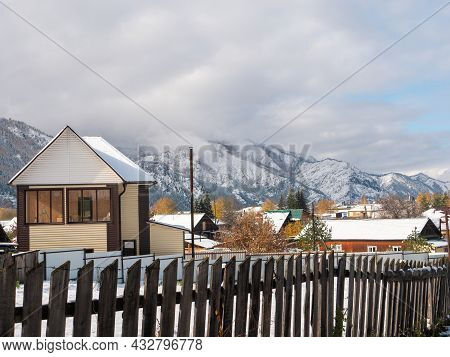 Russian Village Chemal In The Snow. Houses Covered With Snow Against The Background Of The Altai Mou