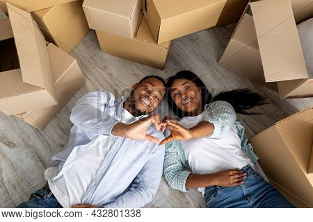 House Ownership. Cheerful Black Spouses Making Heart Shape Gesture While Lying On Floor Near Boxes O
