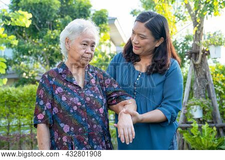 Asian Elderly Woman With Caregiver Walking With Happy In Nature Park.