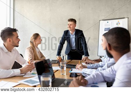 Corporate Meeting Concept. Confident Businessman Talking To Diverse Coworkers In Conference Room