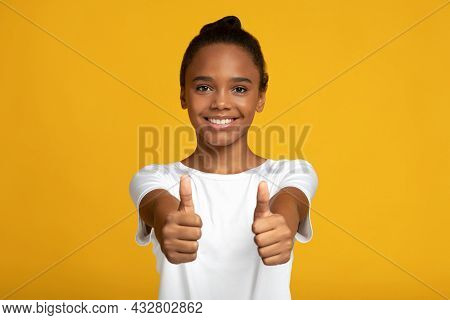 Satisfied Smiling Pretty Adolescent African American Girl Pupil In White T-shirt Showing Thumbs Up G