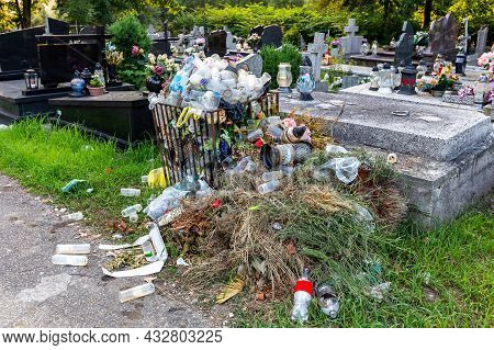 Trash Container Overflowing With Used Lamps, Candles, Artificial Flowers And Wreaths And Other Grave