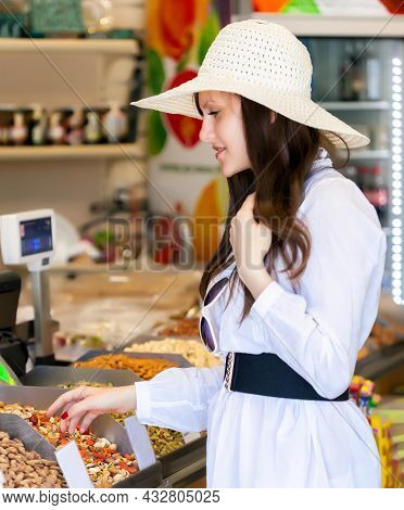 Smiling Woman In A Store Is Buying Nuts