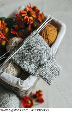 Hand Knitting Sock With Needles And Yarn Balls On A Dark Wooden Background.  Concept For Handmade An