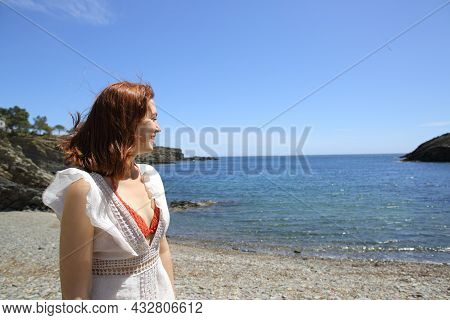 Happy Woman Contemplating Views Walking On The Beach On Summer Vacation