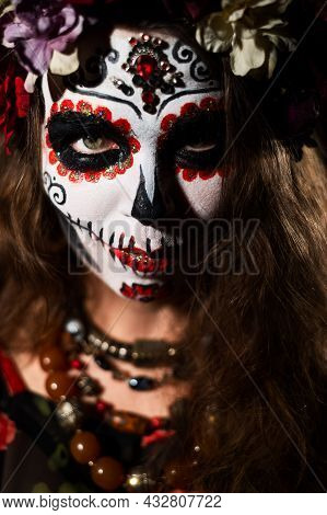 Woman In Santa Muerte Makeup On A Black Background. Girl Wearing Traditional Mexican Holy Death Cost