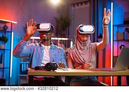 Young Multicultural Couple Playing Games In Virtual Reality Goggles. Black Man And Arabian Woman Sit