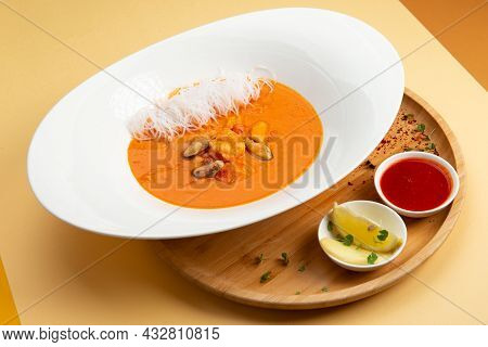 Traditional Soup Tom Yam. In A Plate On A Light Background.