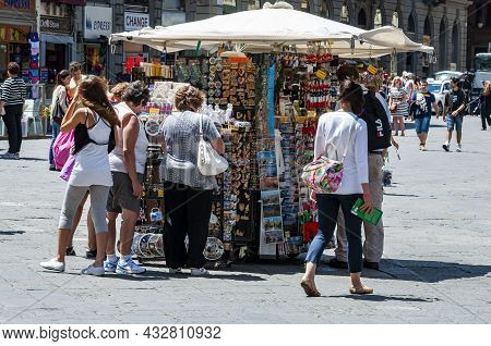 Firenze, Italy - June 11, 2012: Tourists Buying Souvenirs At A Kiosk In A Main Square In Florence, I