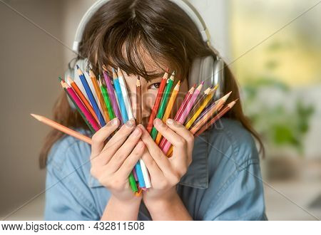 portrait of young pre-teen girl listening music with headset and holding pencils, on-line learning, modern digital techmologies