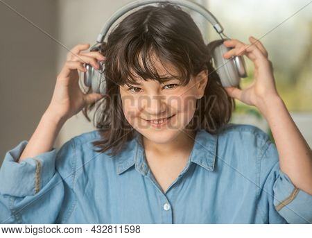 portrait of young pre-teen girl listening music with headset, on-line learning, modern digital techmologies