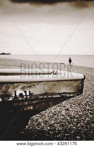 Edge Of Old Wooden Boat With Lonely Female Figure On Pebble Beach And Remains Of The West Pier In Di