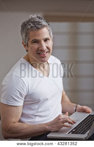 Portrait Of A Man Using A Laptop And Smiling