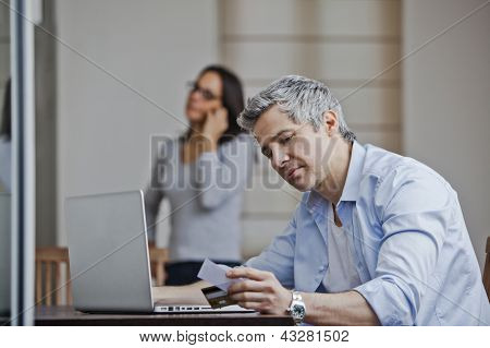 Man Doing Online Shopping With His Wife Talking On A Mobile Phone