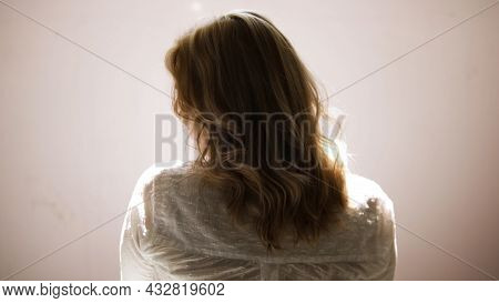A Young Woman Shaking Her Blond Curly Hair Isolated On A Beige Wall Background. Art. Rear View Of A