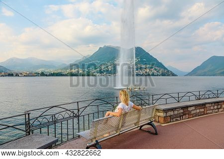 Woman Looking The Water Jet Of Paradiso Fountain Of Lugano City In Lugano Lake Of Switzerland. Sitti