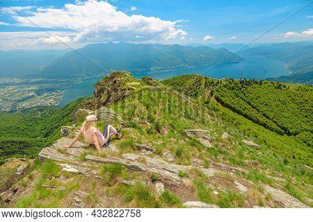 Relaxing Woman Taking A Break After Trekking, Sitting On Top Of Cardada-cimetta Mount In Switzerland