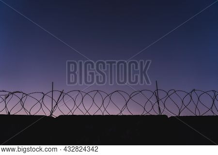 Barbed Wire Prison Wall. Sunset. Panorama. Magenta Sky