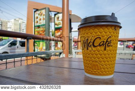Paper Yellow Glass Glass With Coffee For Mccafe Drinks On The Table Against Blurred City From Mcdona