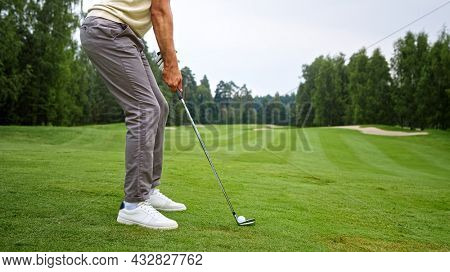 Young golfer in uniform making a hit with a club on the field