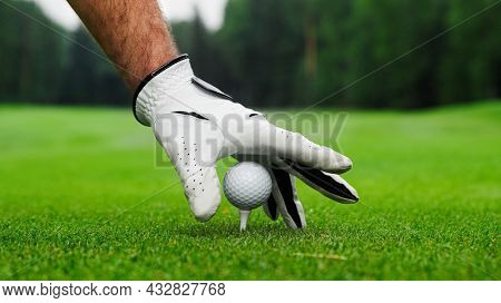 Male hands in a white glove put a golf ball on the course