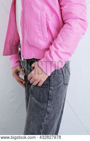 Caucasian Woman In Gray Jeans In A White T-shirt In A Pink Jacket. White Background.