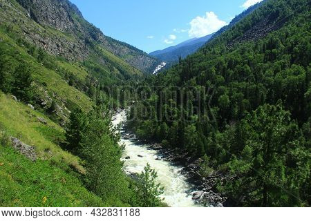 The River Of Uchar Waterfall In Altay Is High In The Mountains On A Clear Summer Day, On The Banks O