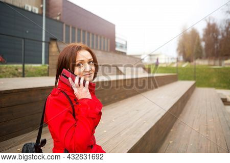 A Woman In A Red Raincoat Is Talking On The Phone Near A Business Center. A Brunette With A Bob Hair