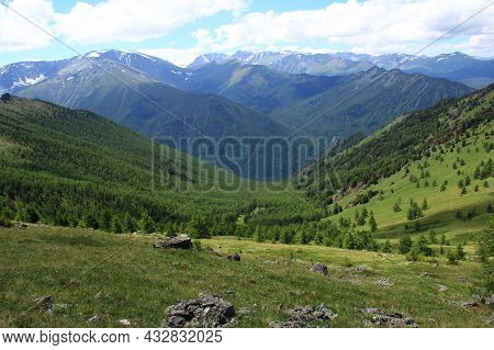 Alpine Valley In Altay With Ridges And Snow-capped Peaks, The Slopes Are Covered With Dense Forest,